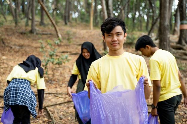 Voluntário de sorriso masculino que guarda o saco de lixo