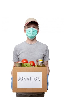 Voluntário em luvas de proteção azuis mostrando alimentos na mercearia caixa de doação