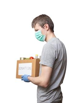 Voluntário em máscara de medicamento, luvas protetoras segurando comida de mercearia em caixa de doação de papelão.