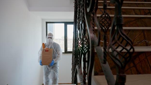 Voluntário em traje anti-risco entregando comida de caridade durante covid-19.