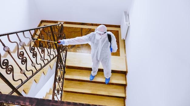 Voluntário em trajes de materiais perigosos pulveriza desinfetante contra a propagação de covid-19.