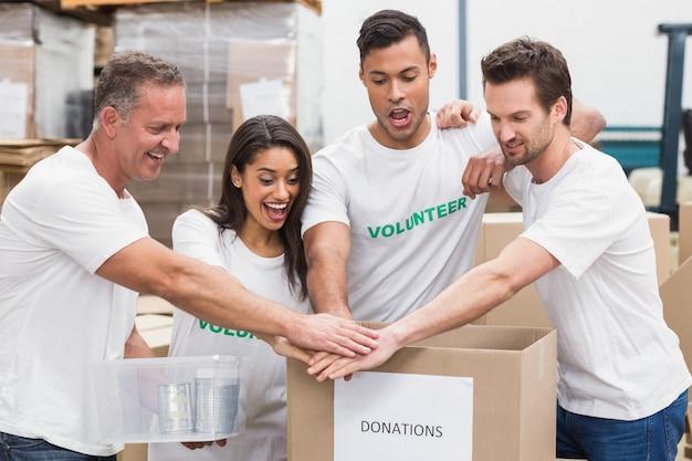 Voluntário equipe de mãos dadas em uma caixa de doações
