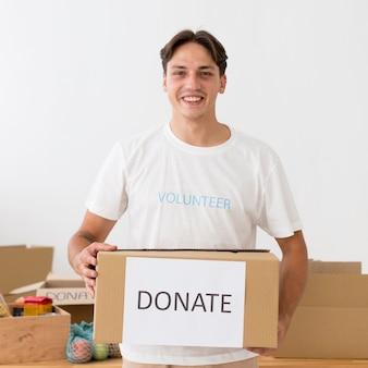 Voluntário feliz segurando uma caixa de doações