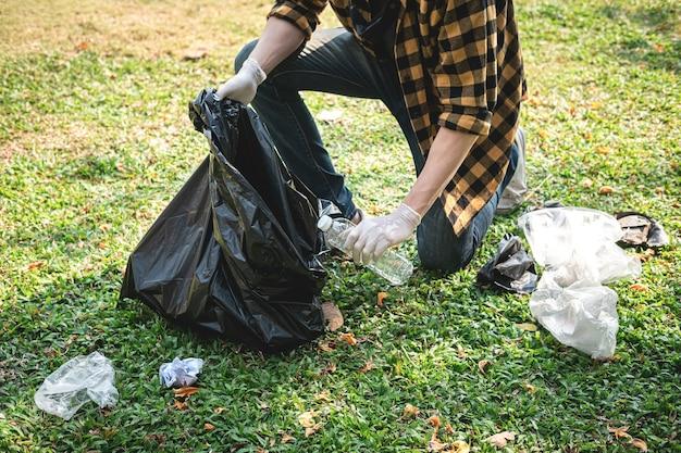 Voluntário, homem de luvas sentado, recolhendo garrafas de plástico e resíduos de plástico em um saco plástico preto para limpeza do parque durante atividades ambientais e coleta de lixo