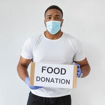 Voluntário masculino com máscara médica segurando uma caixa de doação