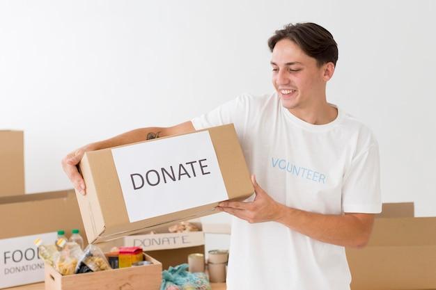 Voluntário segurando uma caixa de doações