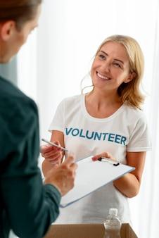 Voluntário sorridente ajudando pessoa necessitada