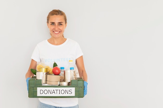 Voluntário sorridente com luvas segurando uma caixa de doações de alimentos