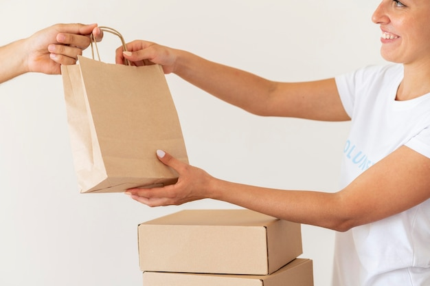 Voluntário sorridente entregando sacola de doações de alimentos