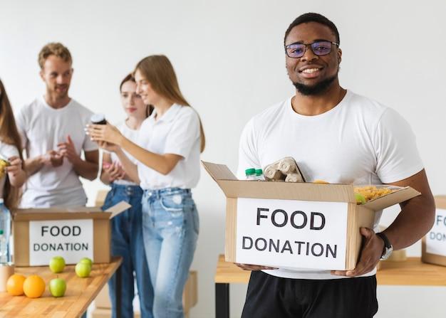 Voluntário sorridente segurando doações de alimentos