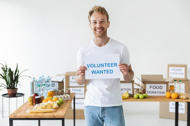 Voluntário sorridente segurando um papel em branco