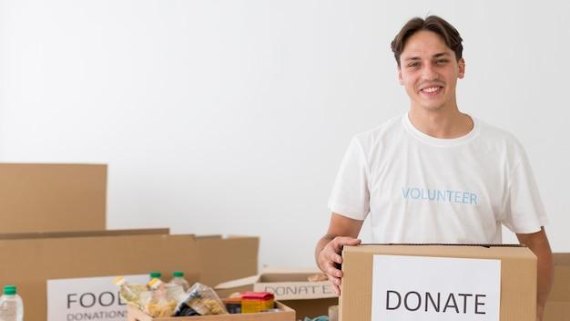 Voluntário sorridente segurando uma caixa de doação com espaço de cópia