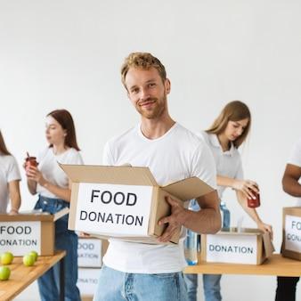 Voluntário sorridente segurando uma caixa de doações de alimentos