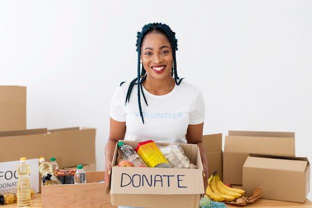 Voluntário sorridente segurando uma caixa de doações