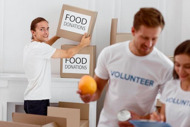 Voluntários ajudando com doações de alimentos para o dia da caridade