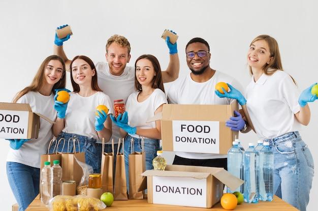 Voluntários alegres posando junto com caixas de doação