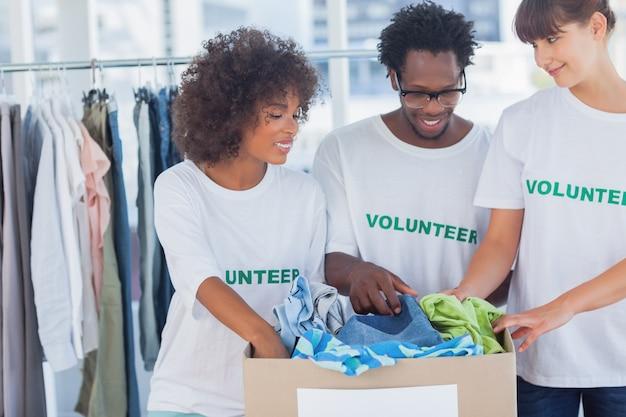 Voluntários alegres tirando roupas de uma caixa de doação
