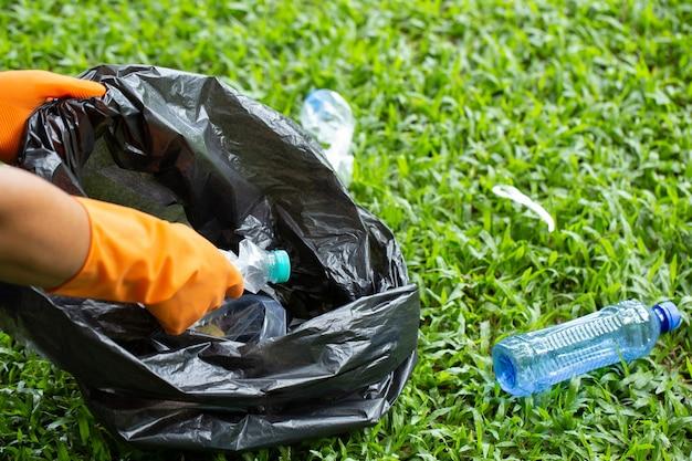 Voluntários amáveis e ecológicos segurando pacotes e recolhendo lixo de garrafas plásticas