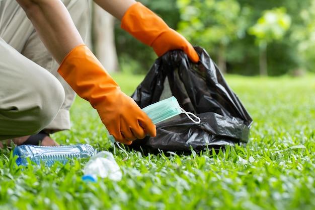 Voluntários amáveis e ecológicos segurando uma máscara facial para prevenir germes e coletar lixo