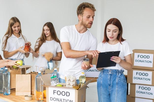 Voluntários colocando alimentos em caixas para doações