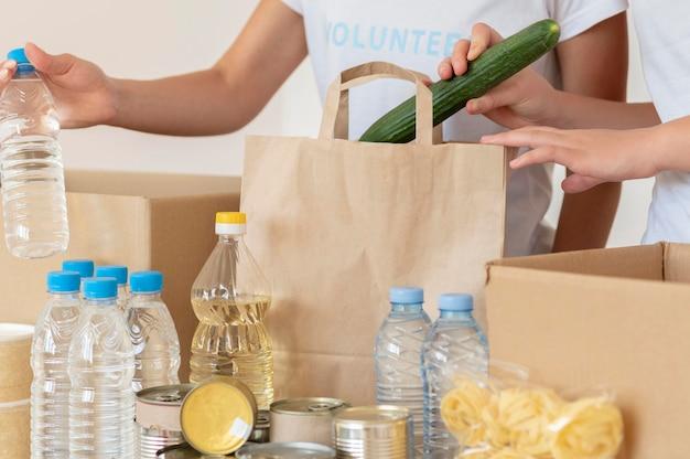 Voluntários colocando alimentos frescos para doação em uma sacola