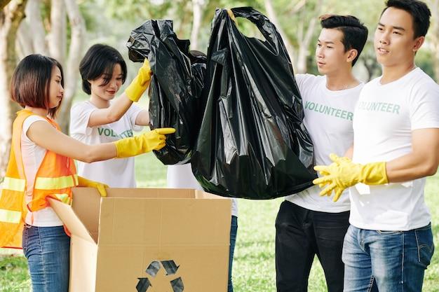 Voluntários colocando sacos de lixo em caixas