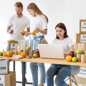 Voluntários com caixas de doação de alimentos e laptop