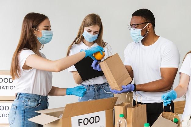 Voluntários com luvas e máscaras médicas preparando caixa com alimentos para doação