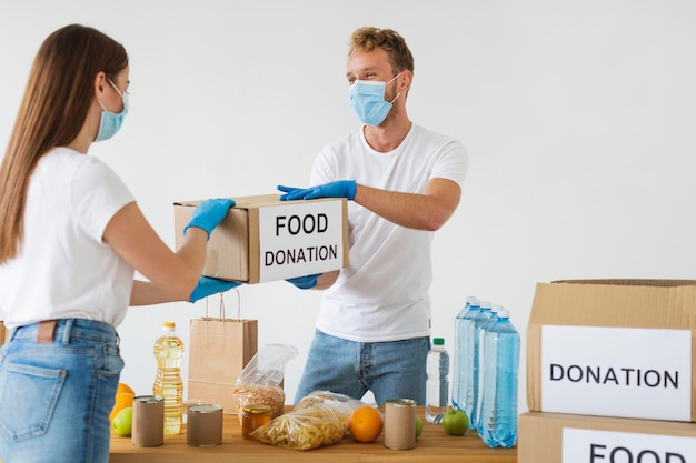 Voluntários com luvas e máscaras médicas preparando caixas de doação
