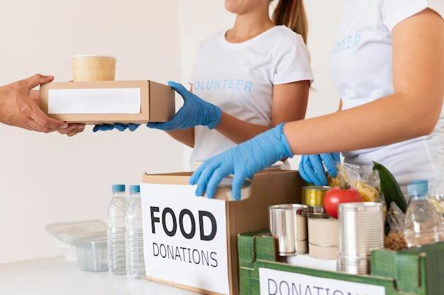 Voluntários com luvas entregando caixas com alimentos para doação