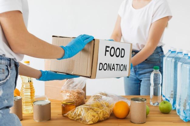 Voluntários com luvas preparando caixas de doação