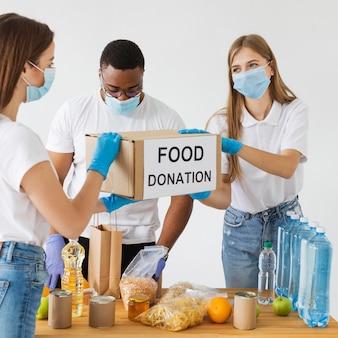 Voluntários com máscaras médicas e luvas preparando caixas de doação