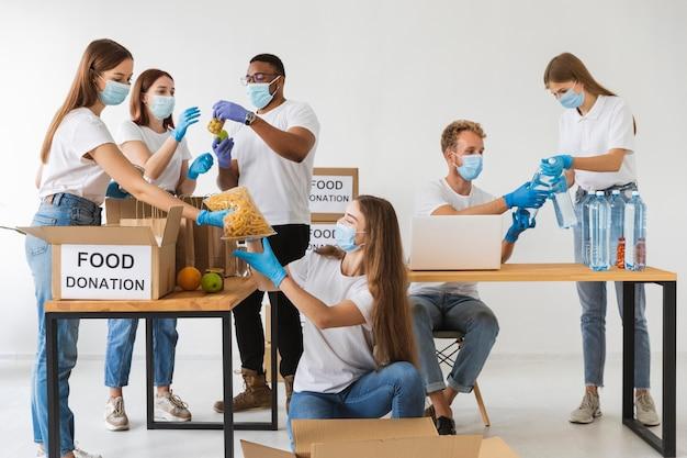 Voluntários com máscaras médicas preparando caixas de doação com provisões