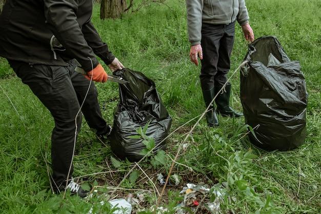 Voluntários com sacos de lixo em viagem à natureza, limpam o meio ambiente.