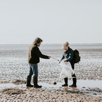 Voluntários de limpeza de praia catando lixo para campanha ambiental