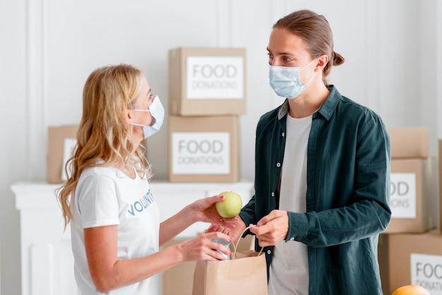 Voluntários doando doações para o dia da alimentação