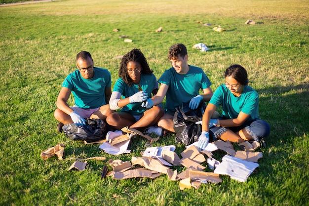 Voluntários ecológicos classificando resíduos de vidro e papel