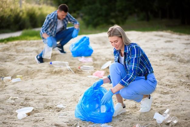 Voluntários felizes com sacos de lixo, limpeza de área no parque