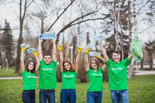 Voluntários levantando garrafas plásticas