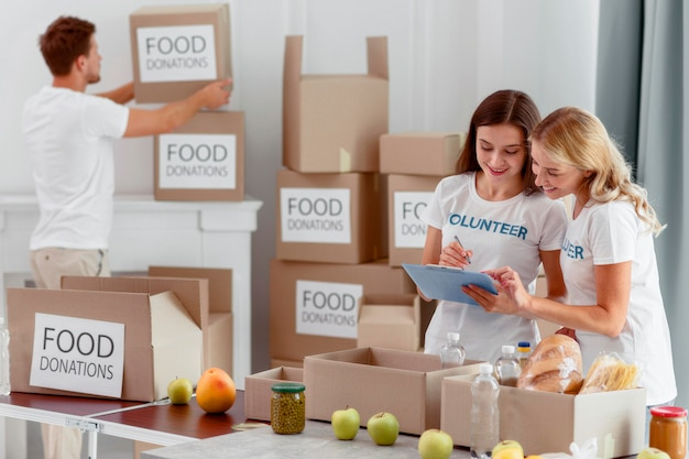Voluntários preparando caixas com alimentos para caridade