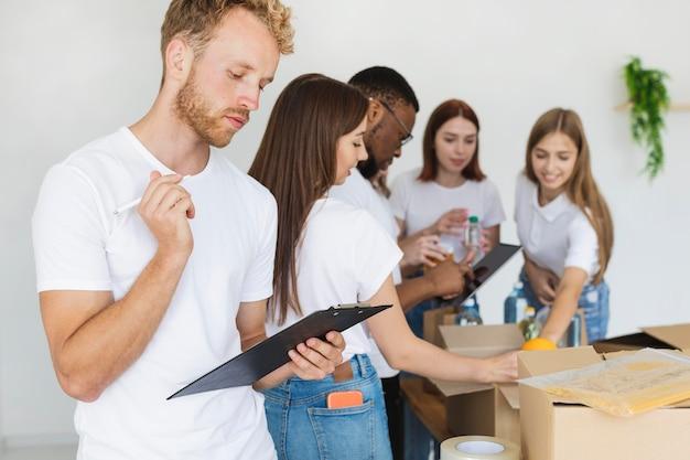 Voluntários preparando caixas com doações de alimentos usando tablet