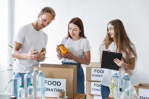 Voluntários preparando caixas para doação com provisões