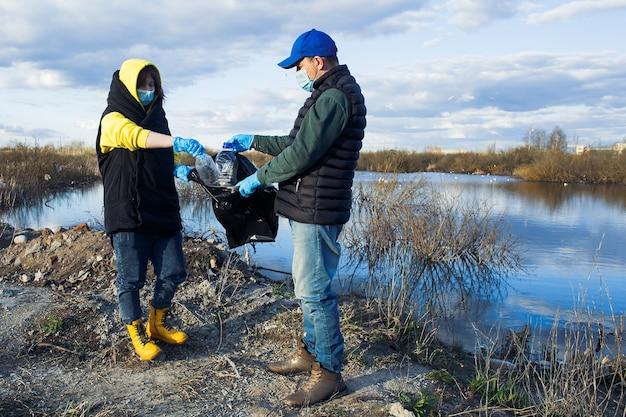 Voluntários recolhem garrafas plásticas em sacos na margem do rio, pelo conceito de ecologia e proteção do solo.