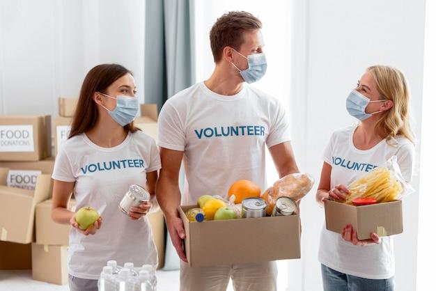 Voluntários segurando caixas de doação de alimentos