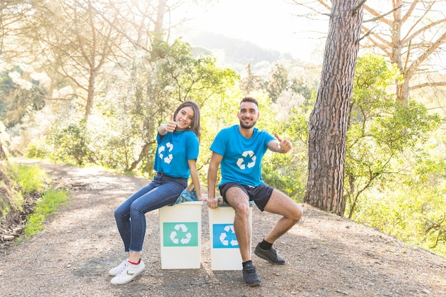 Voluntários sentados em latas de lixo na floresta