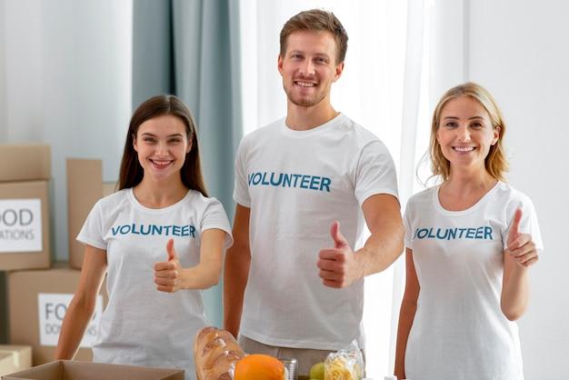Voluntários sorridentes a posar com o polegar para cima