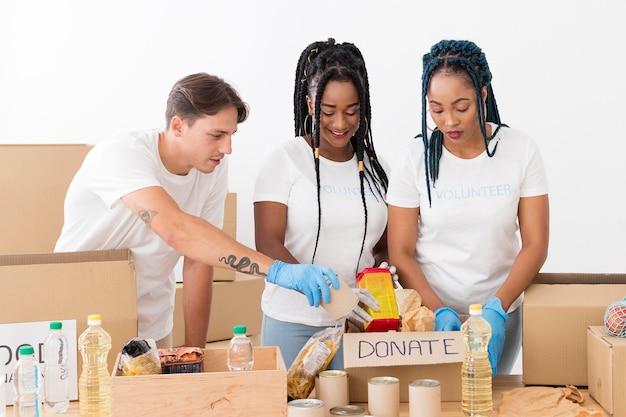 Voluntários sorridentes cuidando de doações