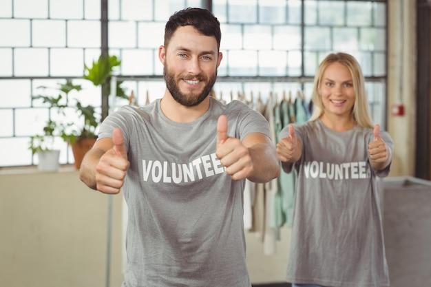 Voluntários sorridentes felizes dando polegares