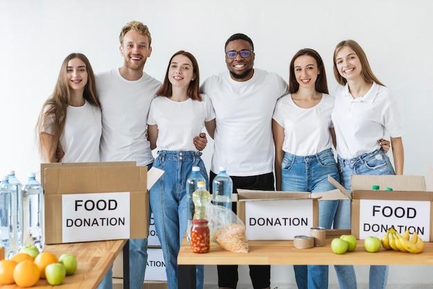 Voluntários sorridentes posando ao lado de caixas para doação
