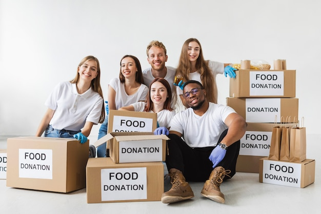 Voluntários sorridentes posando junto com caixas de doação com comida